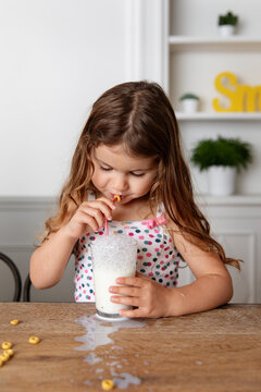 Cute young girl blowing bubbles with straw in glass of milk