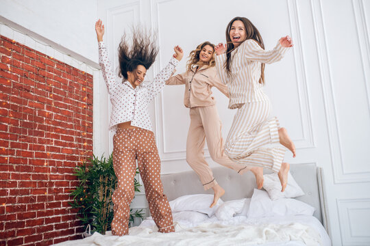 Three young girls jumping on bed and feeling amazing