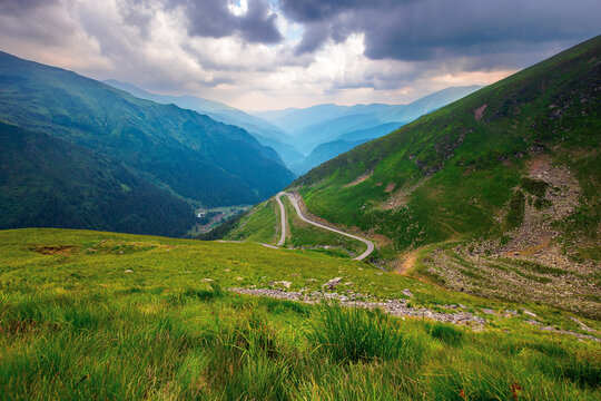 road in high mountains of romania. popular travel destination of fagaras ridge. route 7c is also known as transfagarasan. dramatyc summer weather with clouds on the sky