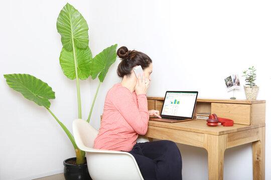Eine Frau sitzt in Ihrem Schlafzimmer am Laptop