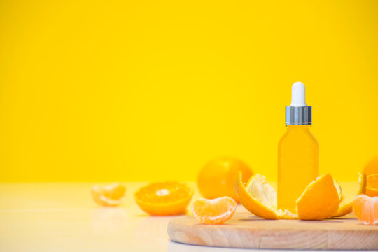 Vitamin C serum cosmetic bottle in tangerine peel with orange pieces on yellow background with copy space. Citrus essential oil, cosmetics aromatherapy. Organic SPA cosmetics with herbal ingredients.