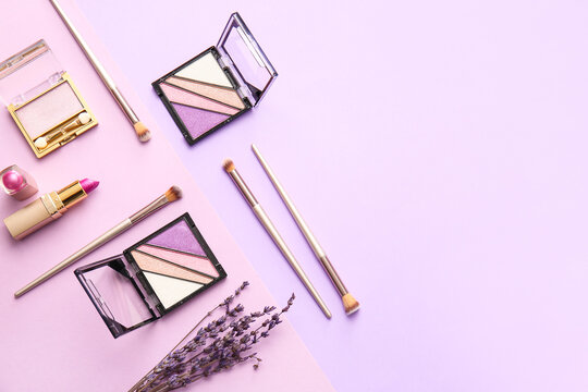 Beautiful eyeshadows, lipstick and brushes on color background