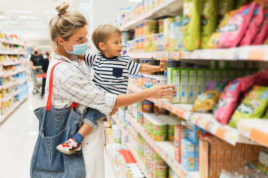 Mother and her little son in a supermarket during virus pandemic