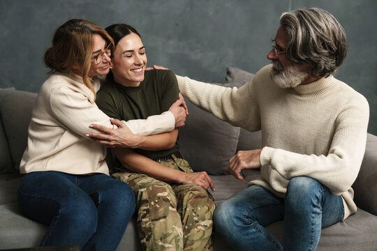 Happy mature parents smiling and hugging with military daughter