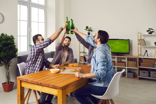 Cheers! Friends sitting at table at home and clinking beer bottles. Group of happy young men eating pizza, enjoying drinks, watching football match on TV, having fun and enjoying good time together