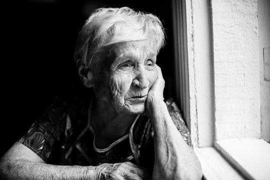 An elderly woman sitting at the table. Black and white photo.