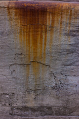 Traces of rusty water stains on the old cement plaster wall.