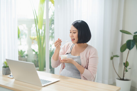 Beautiful pregnant business woman is eating yogurt and smiling while sitting at her working place at home