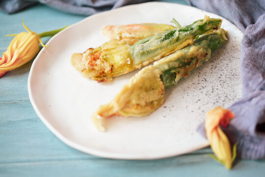 Battered and fried Courgette or Zucchini squash blossoms shot from above over a blue rustic table.