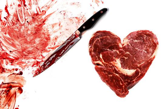 Fresh raw meat in shape of heart, knife and blood splatters