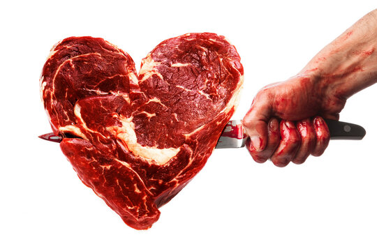Male hand with bloody knife stabbed into the meat in shape of heart