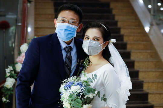 Vietnamese dentist Tran Phuong Thao and her husband Tran Minh Hieu wearing protective masks, pose for a photo at their wedding ceremony during the coronavirus disease (COVID-19) outbreak in Hanoi