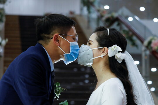 Vietnamese dentist Tran Phuong Thao and her husband Tran Minh Hieu wearing protective masks, kiss at their wedding ceremony during the coronavirus disease (COVID-19) outbreak in Hanoi