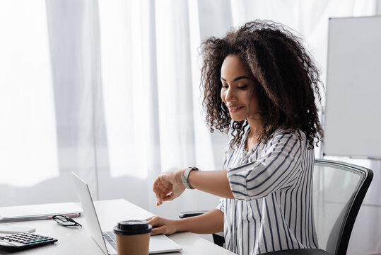 happy african american freelancer looking at watch near laptop and paper cup on desk