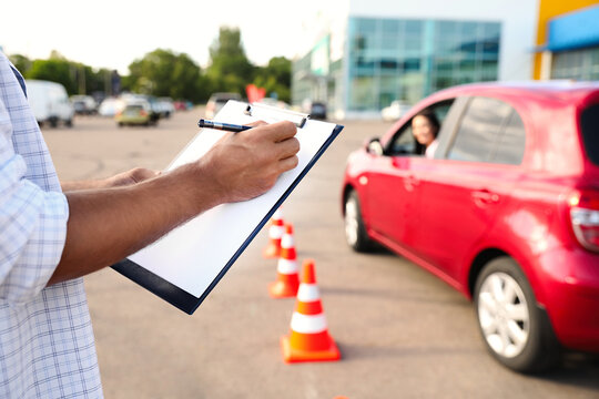 Instructor with clipboard near car outdoors, closeup. Driving school exam
