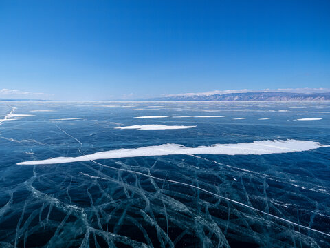 Aerial panoramic view of the Baikal lake at winter season. Spiderweb cracks on frozen ice surface and far mountain on horizon under clear blue sky. Beautiful landscape, perspective view from high.