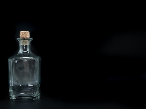 Single empty glass bottle on a black background. Transparent square bottle. Front view of the laying on its side transparent square bottle.