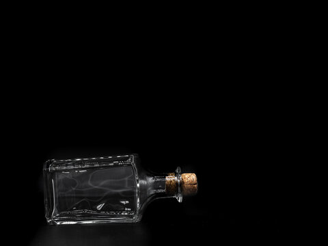 Empty glass bottle closed with cork cap isolated on a dark background. Front view of the laying on its side transparent square bottle.
