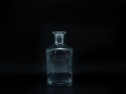 Single empty glass bottle on a black background. Transparent square bottle. Front view of the vertical staying colorless jar.