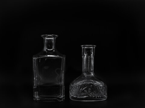 Empty glass carafe and empty glass bottle isolated on a black background. Pair of the transparent bottles. Front view of the two upright jars with different shape.