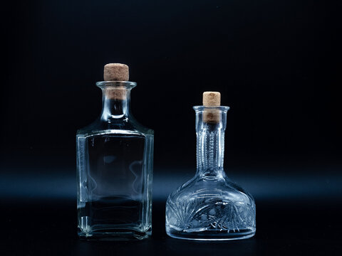 Empty glass carafe and empty glass bottle closed with cork caps isolated on a black background. Pair of the transparent bottles. Front view of the two vertical staying jars with different shape.
