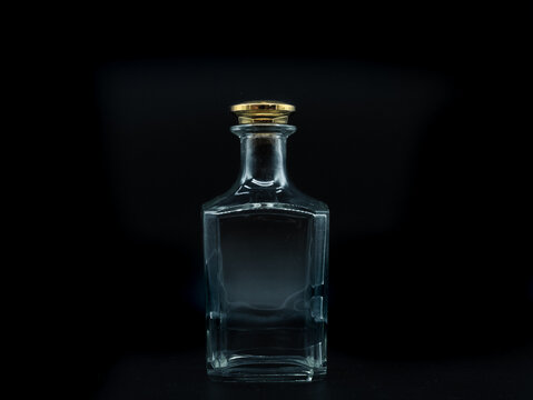 Empty glass bottle closed with big golden round cork isolated on a black background. Transparent square bottle. Front view of the vertical staying jar.