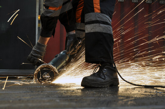 Worker at the factory cuts metal. sparks.