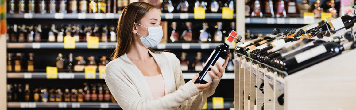 Young woman in protective mask choosing wine in supermarket, banner