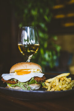 Vertical shot of a tasty burger with French fries on the side and a drink