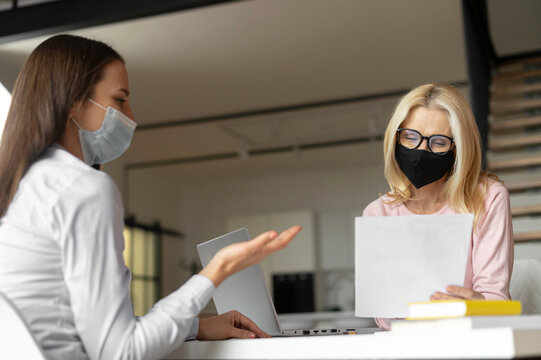 Confident female hr manager sitting at the office, wearing face mask, training young female worker intern, interviewing job seeker, mentoring a student. Social distance and safety at work concept