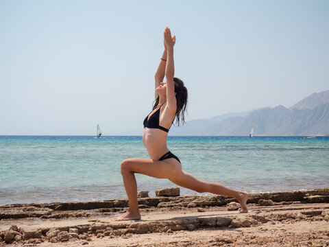 Young brunette woman doing yoga exercises on the beach near sea