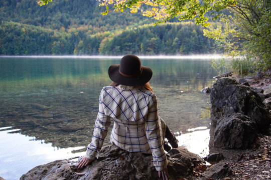 A person sitting and relaxing by an alpine lake