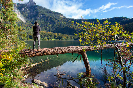 A person looking across a clear alpine lake on a sunny day in Germany