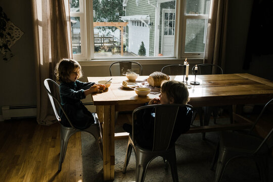 Two kids eating soup and bread for lunch together at the table