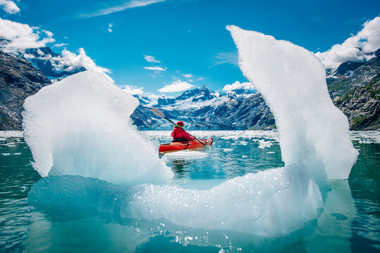 Woman kayaking in Glacier Bay National Park with iceberg in foreground