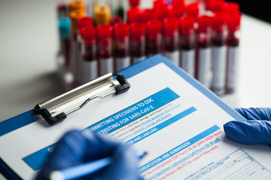 Lab technician filling out specimen submitting form