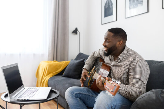 Smiling young African American male musician playing guitar during an online concert at home while isolated during coronavirus, sitting on the sofa, using a laptop to stream record or teach music