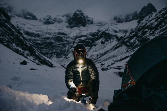 Man Making Tea Close to the Tent in Switzerland Mountains Winter