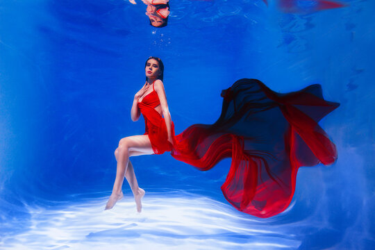 young woman in a red dress on the water. Girl swims in the water in a dress with a long train