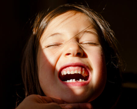 A small girl with eyes closed tilting up head to show first lost tooth
