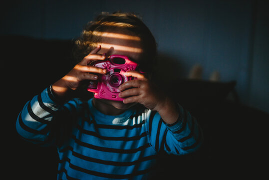 Young child pretending to take a photo with toy camera inside at home