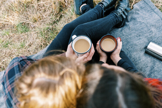 Cute lesbian couple sitting on blanket after hike drinking coffee from thermos