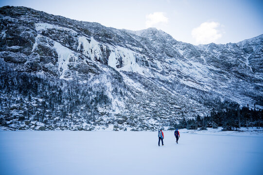 Two male climbers walk across a frozen lake with mountains behind them