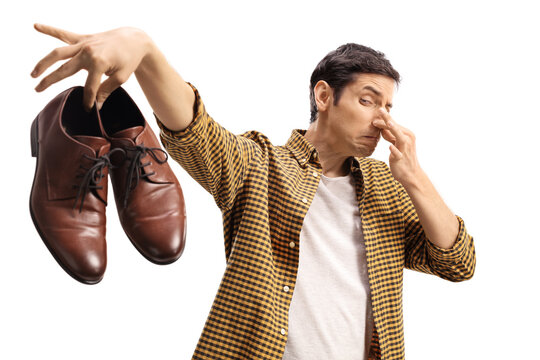 Man blocking his nose and holding a pair of smelly shoes