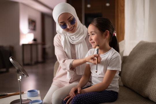 Muslim mother teaching daughter to apply makeup