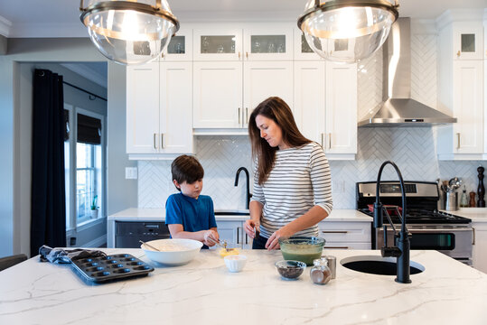 Mother and son making muffins together in a modern white kitchen.