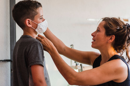Mother putting the mask on her child