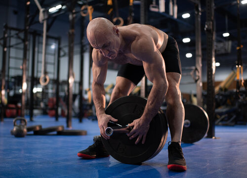 Bald senior athlete preparing for weightlifting training