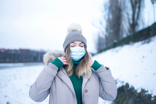 portrait of a woman in a mask in winter,  a girl in a jacket and a respirator, protection against coronavirus, health care, self-isolation