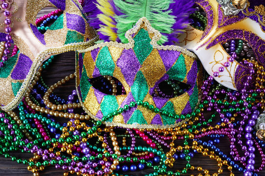 A group of Venetian and New Orlean Mardi gras mask with colorful beads on dark background